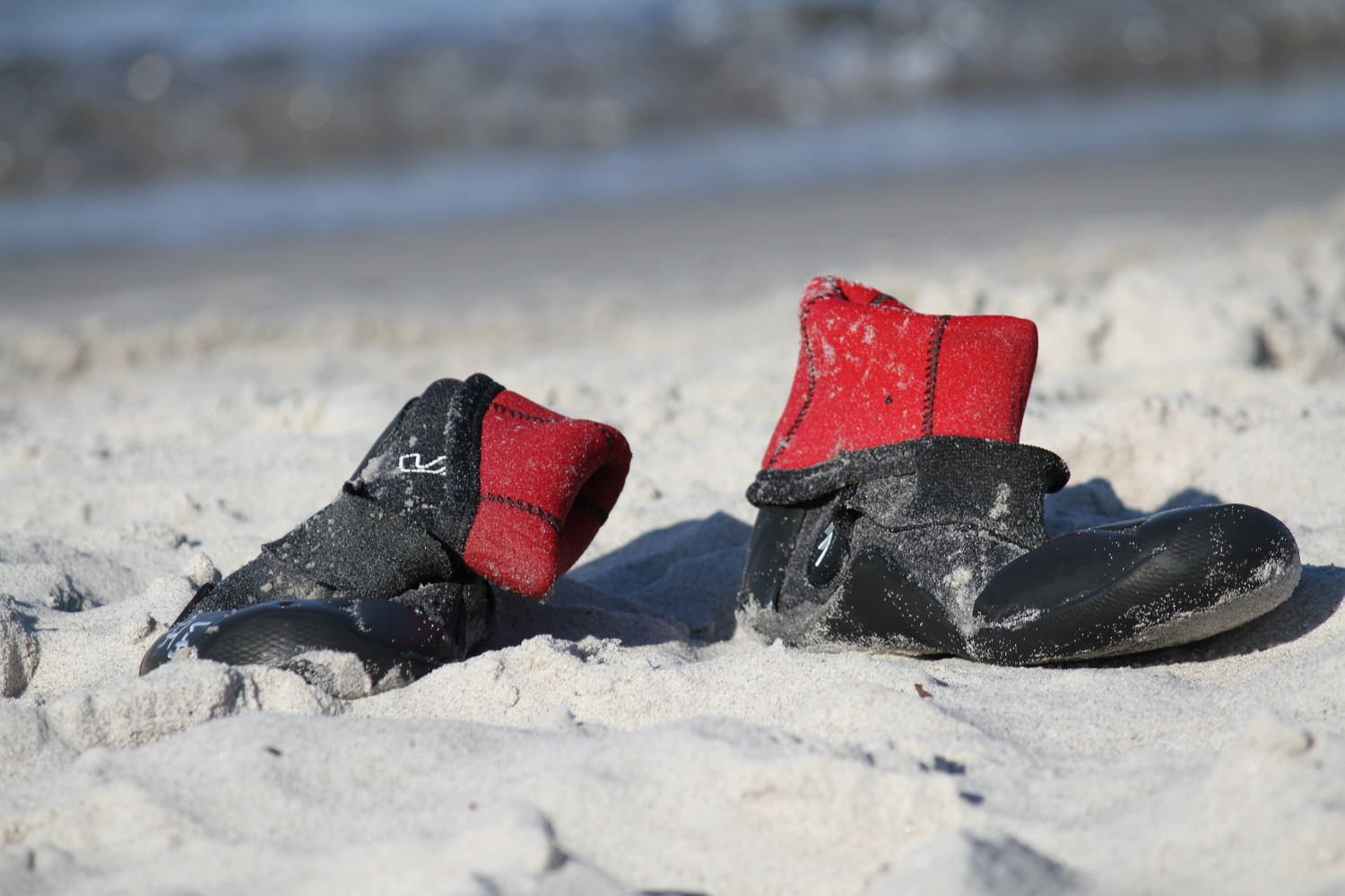 wetsuit booties sitting in sand