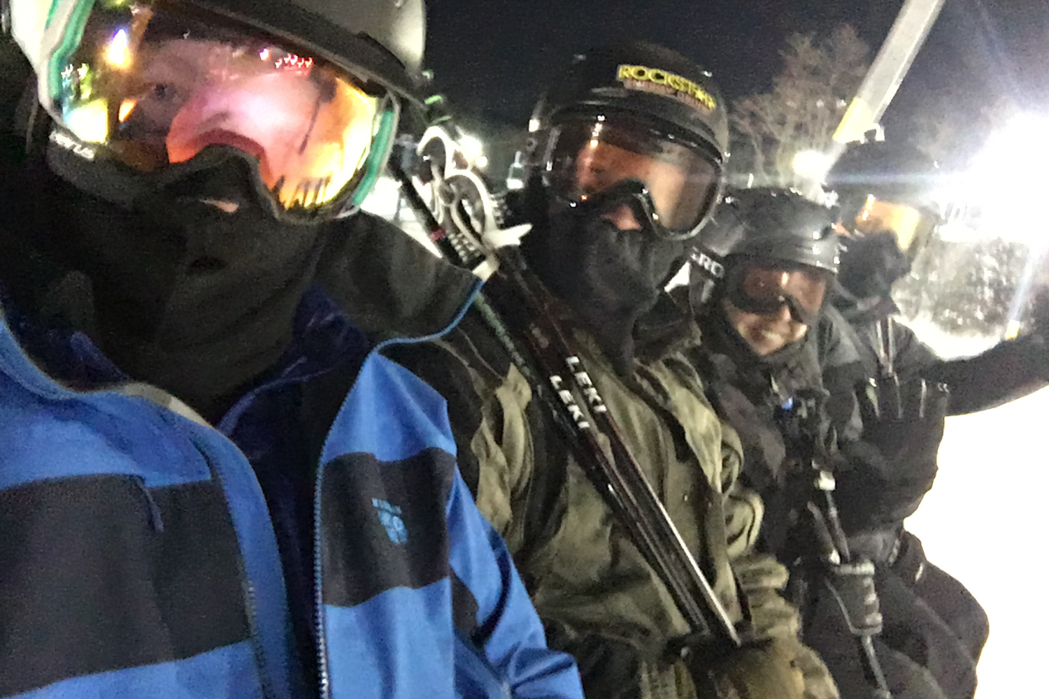 riding chairlift while night skiing wearing ski goggles