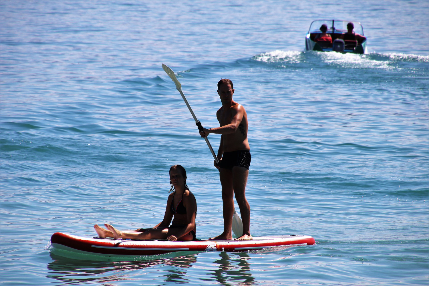 a couple paddling on inflatable sup