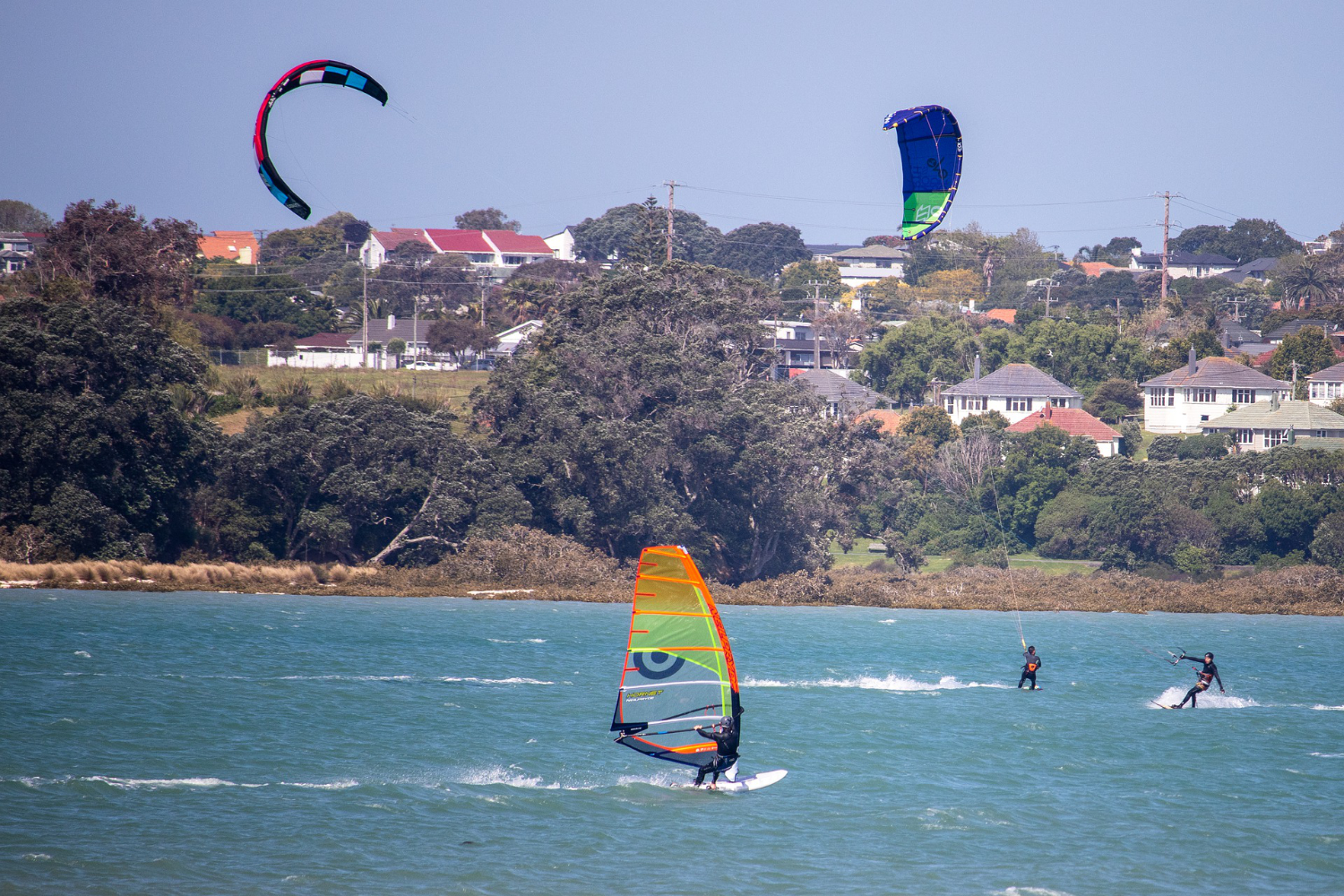 kiters and windsurfers by shore